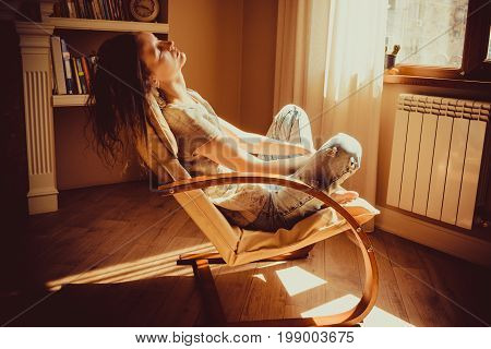 Woman relaxing and napping in comfortable modern chair near window radiator, livingroom. Warm natural light. Cozy home. Casual clothing. Casual style indoor. Room interior. Tired and thoughtful woman.