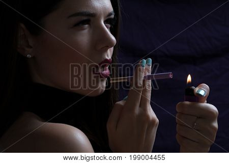 Portrait of the beautiful elegant girl smoking cigarette isolated on dark background with lighter and fire.