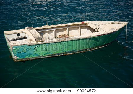 Small old fishing boat floats on water