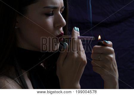 Portrait of the beautiful elegant girl smoking cigarette isolated on dark background.