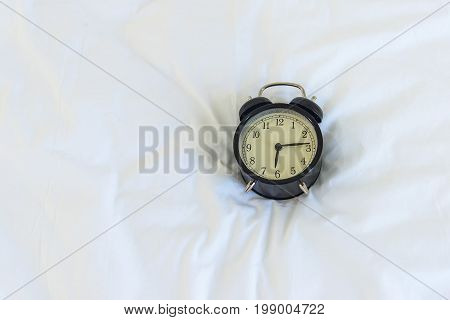 Alarm clock on bed in morning with sun light soft and select focus