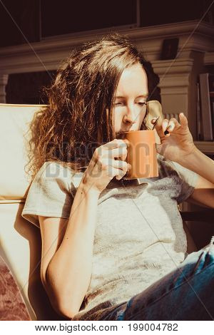 Enjoying time at home. Close up portrait chestnut hair woman relaxing in comfortable chair at window drinking tea or coffee. Natural light. Cozy home. Enjoy moment. Bright sunny day. Cup Hot Beverage
