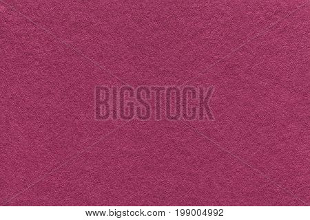 Texture of old purple paper background closeup. Structure of dense magenta cardboard.
