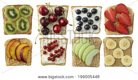 Sandwiches with peanut butter and cream cheese. Fresh healthy appetizer snack with bread. Sandwiches on bread topped with fresh strawberry cherry currant banana apple nectarine and kiwi. Healthy breakfast with toasts. Top view.