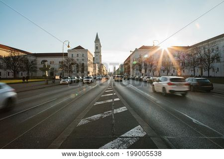 View of the road on the street Leopoldstrasse in Munich, Germany. Fast blurred motion car on sunset background.