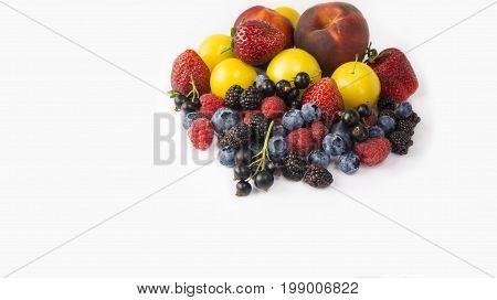 Ripe blueberries raspberries black currants blackberries strawberries yellow plums and peaches on white background. Berries with copy space for text. Background berries. Various fresh summer berries.