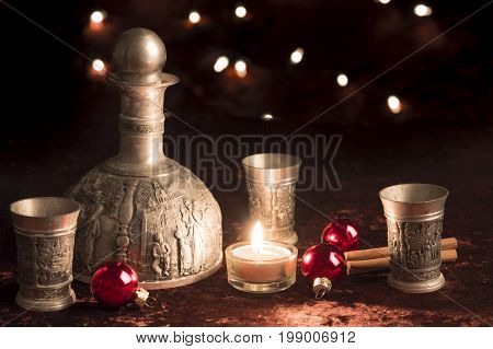 Old wine jug pewter at Christmas with candle and baubles