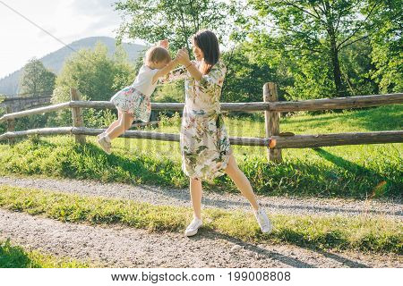 woman play around with her daugher on the country road