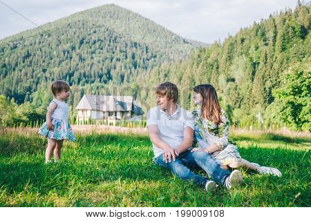 parents play with daughter on the field with mountains with forest on background