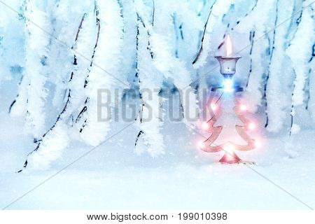 Beautiful christmas tree in a snowy park. A metal candlestick in the form of a New Year's spruce. New Year's art image in blue tones. In the woods the snow falls.