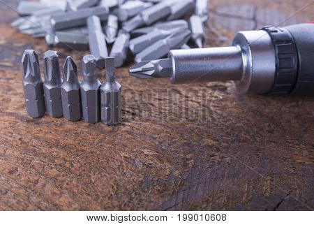 Metal screw driver heads bit with screwdriver on the wood