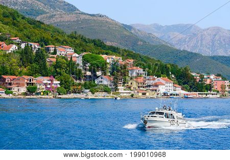 KOTOR BAY MONTENEGRO - SEPTEMBER 16 2015: Beautiful view from sea on coast and resort village at foot of mountains Kotor Bay Montenegro. Unidentified people sail on boat