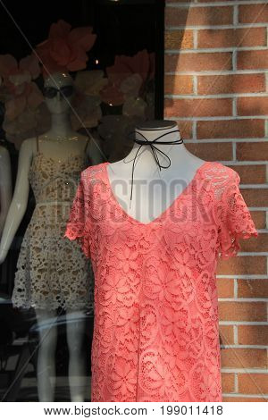 Vertical image of crochet dresses on mannequins outside storefront