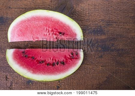 Two watermelon slices on the wooden board opposite each other