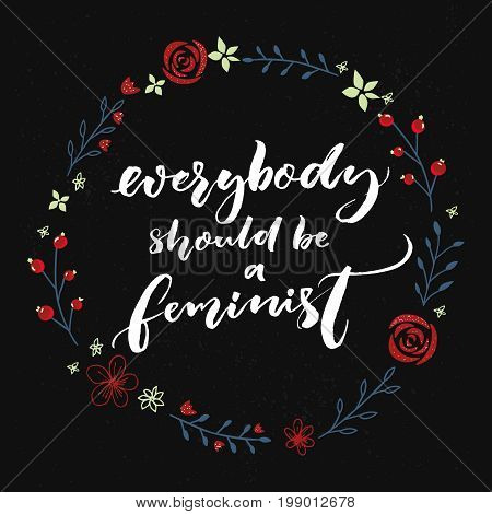 Everybody should be feminist. Feminism quote, brush calligraphy on black background with floral wreath.