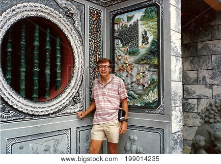 SINGAPORE / CIRCA 1990: An American tourist poses for a photograph in the Kwan Im Thong Hood Cho Temple.