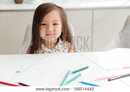 Image of pretty little cute asian girl at home indoors drawing with pencils. Looking camera.