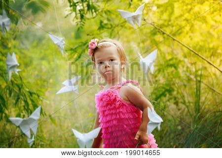 child near paper butterflies. little girl in the bushes lit by sunset rays.
