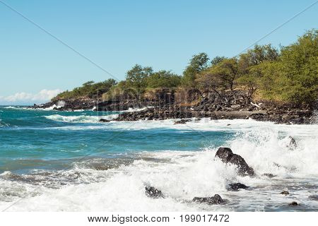 Rugged coastline of north shore on the Big Island of Hawaii. Waves crash on low cliffs on a sunny day with blue sky and a few clouds.