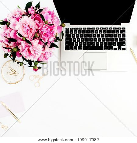 Flat lay home office desk. Female workspace with laptop pink peonies bouquet golden accessories pink diary on white background. Top view feminine background.
