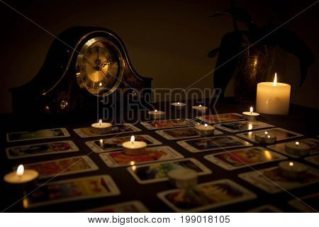 Mystic fortune-telling with fired candles and playing cards in dark on wooden background