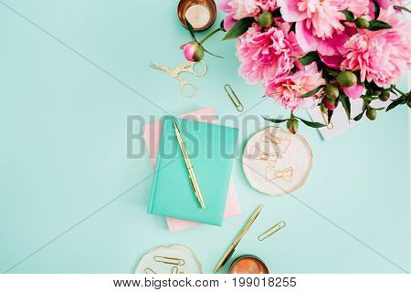 Flat lay home office desk. Female workspace with pink peony flowers bouquet golden accessories pink and mint diary on mint background. Top view feminine background.