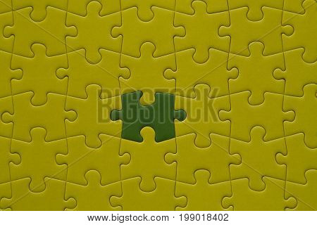 Yellow jigsaw puzzle and one piece green.