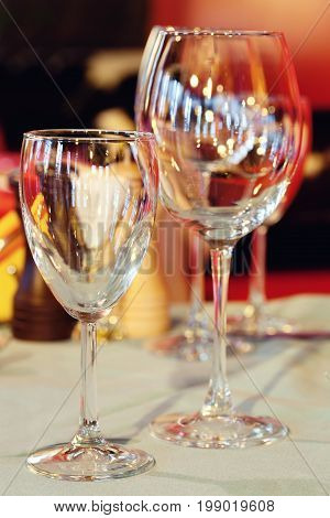 Beautiful wine glasses tableware close-up, restaurant service concept. Bright blurred and colorful interior, selective focus.