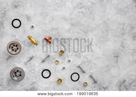 Drain parts and plumbing tools on grey stone background top view.