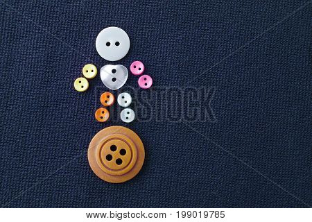 Cute sewing buttons man. Funny character with love white heart button. violet textile background. macro view, soft focus.
