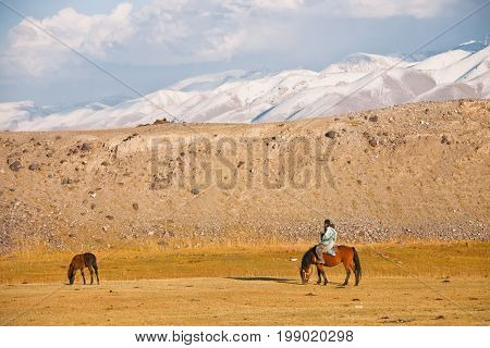 Shepherd on a horse and foal in the mountains of Tien Shan. The Issyk-Kul region Kyrgyzstan Asia snow rocks pasture