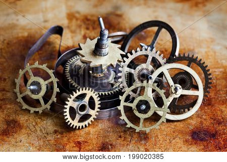 Vintage cogs gears wheels collection set. Aged clockwork mechanism parts macro view. Different cogwheels teeth shapes objects with textured metal surface. Shallow depth of field photo.