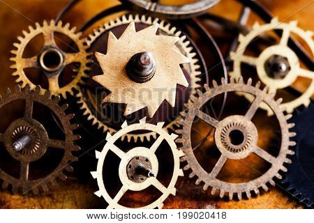 Aged clockwork mechanism parts macro view. Different cogwheels teeth shapes objects with textured metal surface