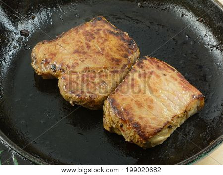 Grilling New York Strip Steak for two with olive oil in cast iron frying pan skillet