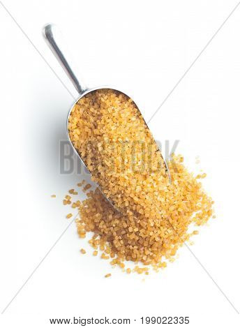 Brown cane sugar in scoop isolated on white background. crystalline brown sugar. Top view.