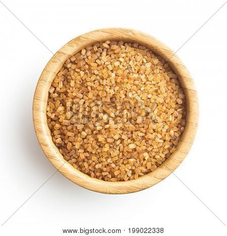 Brown cane sugar isolated on white background. Sweet sugar in bowl. Top view.