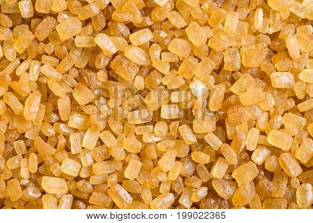 Texture of brown cane sugar. Sweet crystalline sugar. Top view on brown sugar.