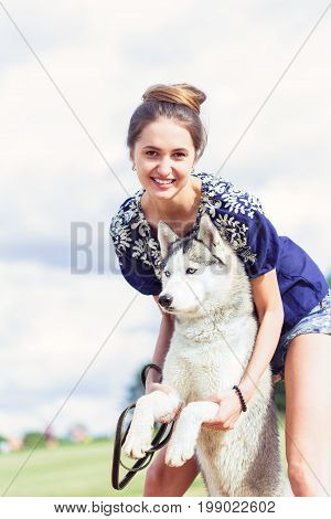 Young woman playing with her Husky dog outdoors. Siberian husky.