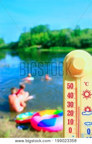 thermometer with indication 31 degrees and bathing people. People swim in the river in hot summer