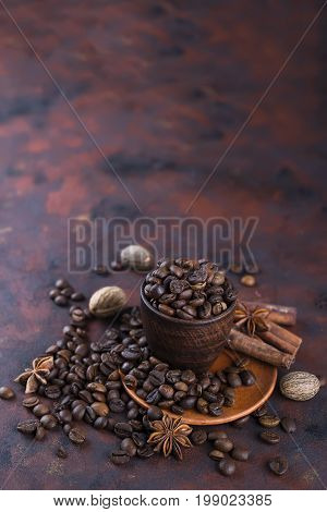 coffe beens with spices on a brown stone background. Ingredients for aroma coffe anise, cardamon, cinnamon,