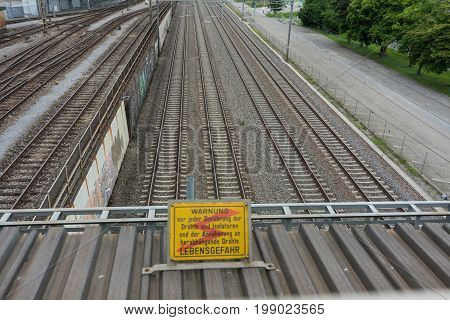 attention high voltage sign near train tracks in german language