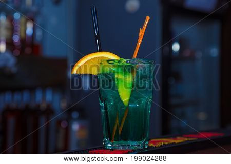 A beautiful green cocktail with slice of orange in a tall glass. close-up