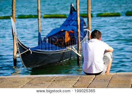 Venice, Italy - July, 28, 2017: man sits near the gondola in Venice, Italy