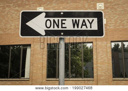 One way sign in front of a brick building