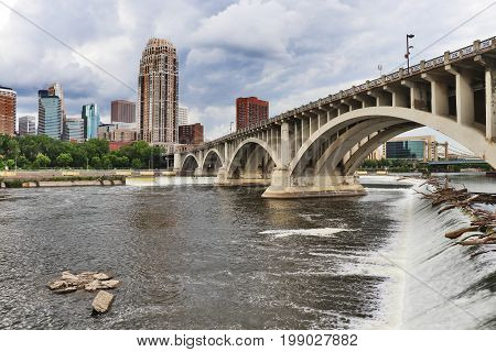 Minneapolis downtown skyline and Third Avenue Bridge above Saint Anthony Falls Mississippi river. Midwest USA Minnesota state.