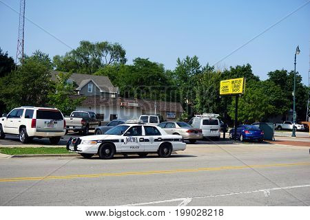 JOLIET, ILLINOIS / UNITED STATES - JULY 17, 2017: A white Joliet police car is parked on Madison Avenue in Joliet.