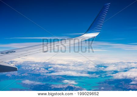 The wing of the plane against the sky and clouds. View of the wing tip of the aircraft. Wing of an airplane against a background in the sky. A view of the wing of an airplane on the background of the earth.
