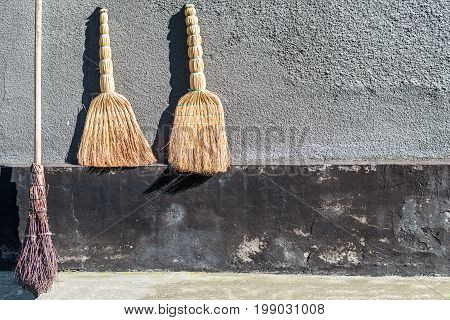 The sampler brooms for cleaning and the factory two brooms against the background of a gray wall