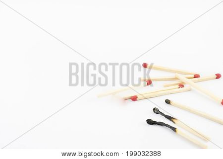 Heap with burnt and unburned matches on a white background.