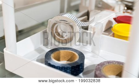 Rolls of masking tapes with cute patterns in dispenser stand on white shelf . Selective focus.